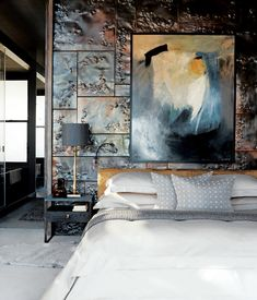 Custom hammered-copper tiles add texture and reflect light in the master bedroom of a Cape Town, South Africa, penthouse. The bed, steel-and-walnut side tables, and brass lamps are all custom-made by Cécile & Boyd's.