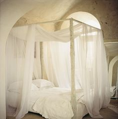 Une chambre chaleureuse avec lit à baldaquin ancien drapé de voilages