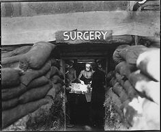 """""""In an underground surgery room, behind the front lines on Bougainville, an American Army doctor operates on a U.S. soldier wounded by a Japanese sniper, 13 December 1943."""" (US National Archives)"""
