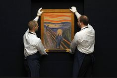 Employees at Sotheby's hold Munch's 'The Scream' at the New York auction house. Photograph: Andrew Burton/Reuters