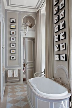 Deniot designed the master bath's tub surround, limestone-and-marble floor, and paneling, which is decorated with framed butterfly specimens from Deyrolle; the lantern is by Vaughan, the curtains are made of a Pierre Frey satin, and the tub fittings are by Volevatch.
