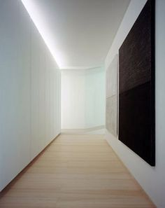 Corridor lighting with indirect cove lighting.  I like the matching reveal at the floor.