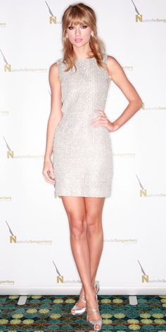 Taylor Swift wore a sparkling silver cord embroidered Houghton sheath, silver jewelry and strappy Jimmy Choo heels.