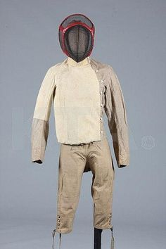 Fencing ensemble, French, late 18th century, comprising padded natural linen jacket with chamois breast and upper right arm, bone buttons down one side, stand collar, the tan calico breeches with similarly buttoned small fall, the wire mesh helmet with red morocco bindings and head brace - by Kerry Taylor Auctions