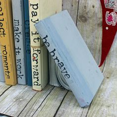 repurposed books make beautiful decor! this is a very simple piece that can have big impact when stacked or grouped with additional books to create a line of one-word statements. on your library shelv