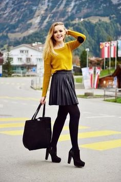 Blonde in black pleated leather skater skirt and ankle boots