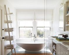 The master bath's vanity, mirror, and wall shelf are custom made, and the bathtub of volcanic limestone and resin is by Victoria + Albert; the bath and sink fittings are by Dornbracht and Lefroy Brooks, respectively, and the glass tiles are by Ann Sacks.