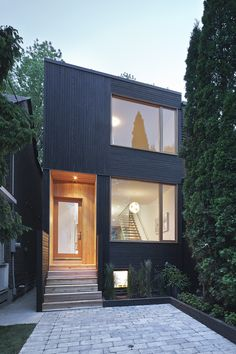 Modern infill home in Toronto has well-configured efficient spaces, a glass enclosed stair, and wood cladding exterior by MODERNest