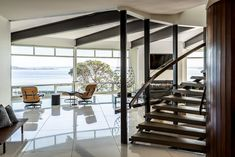 Curved Steel and wood (teak) staircase with Italian quartz stone flooring, steel beams and fireplace beyond