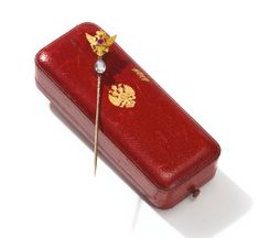 A Fabergé Imperial presentation jeweled gold tie pin, workmaster Alfred Thielemann, St. Petersburg, 1908-1917, the pin surmounted by a chased Imperial eagle centered with a collet-set ruby, with a pear-shaped diamond suspended. According to records of the Imperial Cabinet, this tie pin, priced at 175 rubles, was among items Dowager Empress Maria Fedorovna took with her on her 1909 trip to England.