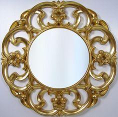 Rama lustra wykonana z masy żywicznej, pokryta płatkami szlaki złotej. Tafla lustra kryształowa, szlif fazowy.
