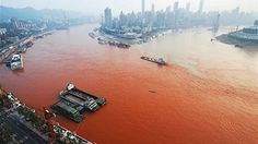 Yangtze River Turns Red In Chongqing (© ChinaFotoPress/Getty Images)China's largest and longest river — looks more like a scene from an apocalyptic sci-fi movie than a bustling port. The river reportedly began turning bizarre shades of crimson yesterday near the city of Chongqing, sending residents swarming to its banks in bewilderment. Some people bottled samples of the ruby-colored fluid while fishermen, apparently too reliant on their trade to pause, went about business as usual. Paired…