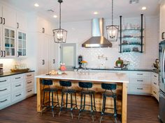The newly renovated kitchen comes with a spacious custom island and dark hardwood floors that offer a nice contrast against the white tile and cabinetry.