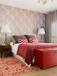 Quarto de casal com decoração em tons de vermelho e muitas estampas.