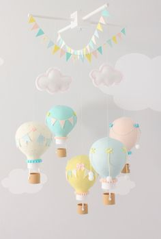 Pastel hot air balloon baby mobile for a cute addition to a travel theme nursery. Yellow, Pink and Aqua balloons float under 2 embroidered clouds. Each balloon is adorned with tiny embellishments, buttons - pompoms - bows and tiny pennant flags. Each basket is 3D printed, which gives it a real wicker texture. The wooden top can be natural wood or painted white. There are two strings of flags hanging from the top for a cute, whimsical touch. Check out the reviews: https://www.etsy.co...