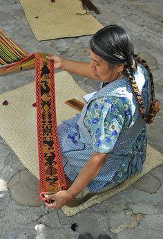 Weaver Margarita Navarro Gomez displays the designs on the fabric she is weaving on her backstrap loom. Santo Tomas Jalieza, Oaxaca, Mexico