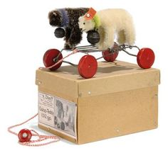 A STEIFF GALOP-TEDDY, (1312g.p.), white mohair polar bear, green mohair ruff, black glass eyes, black stitching, bell and FF button with red cloth tag and a frosted brown mohair bear, purple mohair ruff, brown and black glass eyes, black stitching, bell and FF button, no tag, on eccentric red-wheeled carriage with mechanism causing the bears to move backwards and forwards, original red and white pull cord, the end with wooden knob with FF button, in original plain card box held together with…