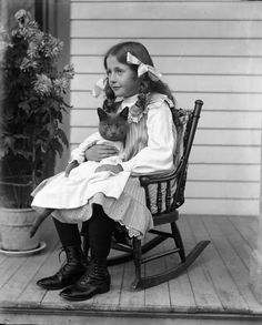 "Alex Krueger, ""Jennie Krueger Bruetzman and Tramp,"" 1905. Archivist's Description: ""Jennie Krueger sits in a rocking chair holding her cat Tramp, who is dressed in baby clothes."" Source: Wisconsin Historical Society."