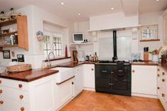 photo of white kitchen with belfast sink flooring wooden worktop worktop parquet flooring and aga