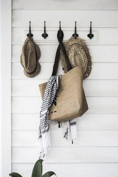 Hooks in the hallway of a pared-back Australian home in neutrals. Photographer: Maree Homer.