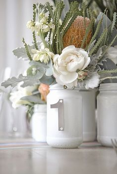 Protea, roses and gray greens in painted white mason jars