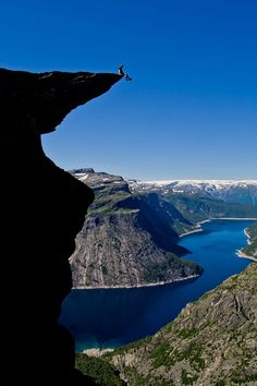 """ON THE EDGE OF TROLLTUNGA, ODDA NORWAY. Don't believe I'd sit on the edge, as this fool is doing.  But, it is a once in a lifetime """"path."""""""