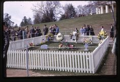 This is the original gravesite of John F. Kennedy, Jr. in Arlington National Cemetery.   On the left is the headstone of his son Patrick Bouvier Kennedy, who was born premature and died after two days. On the right is the cross headstone of his still-born daughter Arabella. Their graves were moved [Patrick from Holyhood Cemetery in Brookline, Massachusetts; Arabella from Newport, Rhode Island] just a few weeks after JFK was assassinated.  In the middle is a mound of evergreen boughs…