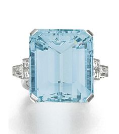 AQUAMARINE AND DIAMOND RING. Set to the centre with a step-cut aquamarine, to shoulders set with similarly cut diamonds