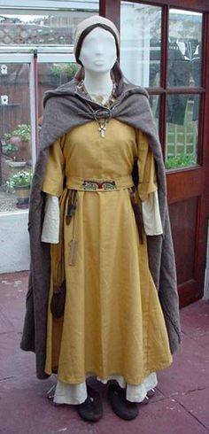 Middle Saxon Woman - During the 6th century there was an influx of Christian missionaries to this country.  The 'tube' dress was discarded and sleeved garments became common. Head-wear was also introduced. The fashion for hanging items off the belt is still very much in evidence.     The individual depicted here is of reasonable status - not high ranking, but not poor either. This is indicated by the color of her clothing, jewellery