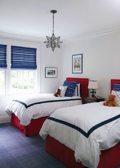 boy's rooms - Worlds Away Clear Star Chandelier red twin headboards nailhead trim red bed skirts blue striped pillows blue striped roman shades white hotel bedding blue border black nightstand cabinet