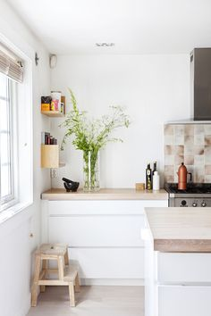 Simple Clean line kitchen. I like the book pile shelfnear the doorway.