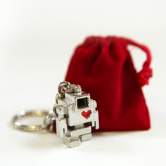 """You guard the keys to your heart. Let Lovebot guard the keys to your house!This 1"""" tall Lovebot is attached to a silver chain and comes in a red velvet keepsake bag. This design is the 1st edition keychain and is limited to 200 pieces worldwide.SOLD OUT"""