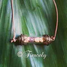 Suede necklace with shell filled glass vial.