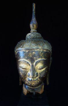 Importante tête de Bouddha exprimant un profond recueillement. Sculpture en bois de teck laqué à trace de dorure. Birmanie Royaume d'Ava XVII eme. (quelques érosions). Ht: 62 cm.