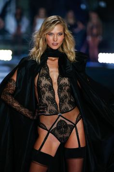 Karlie Kloss makes a dramatic entrance in all-black lingerie & a sweeping cape. | Designer Collection Bodysuit with Swarovski crystals