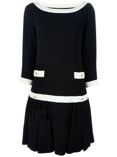Black dress from Moschino featuring a boat neck with ivory trim, two front button ivory panels, an ivory drop waist panel, flared hem and three-quarter length sleeves with contrast buttoned cuffs.