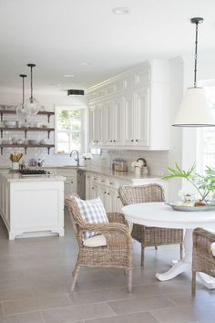 decoracion cocinas, cocina con isla de madera blanca en forma de U, comedor con mesa redonda y sillas de mimbre, suelo con baldosas