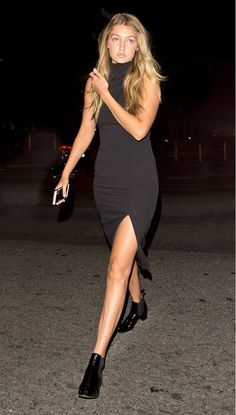 Gigi Hadid wears a high neck black dress with a thigh slit and patent leather booties.