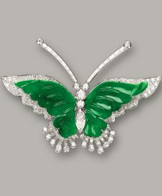 JADEITE AND DIAMOND 'BUTTERFLY' BROOCH The brooch designed as a butterfly, with wings composed of two translucent emerald green jadeite plaques, the antennae set en tremblant with baguette and circular-cut diamonds, embellished by a thorax set with marquise-shaped and brilliant-cut diamonds, decorated by circular-cut diamonds, the diamonds together weighing approximately 3.50 carats, mounted in 18 karat white gold.