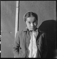 A young Japanese girl at Manzanar Relocation Center, Dorothea Lange, 2 July 1942, public domain via Wikimedia Commons.
