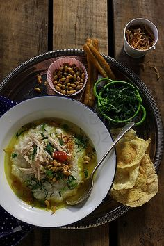 """BUBUR AYAM - Indonesian rice porridge with shredded chicken, soya bean, scallion, fried shallot and curry soup. served with """"emping"""" (crackers made from melinjo / Gnetum gnemon)"""