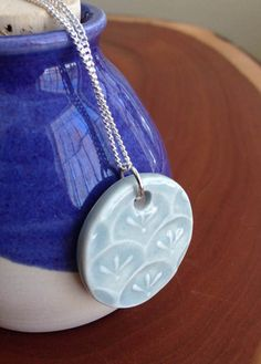 To create this pendant I first had to create a stamp. Each stamp is hand carved, fired in the kiln and then used to create an impression on the porcelain pendant while the clay is still soft. After firing, glaze was applied to highlight the stamp impression. This porcelain pendant is strung on an 18 silver plated chain.  Please note that each pendant is hand made and one of a kind. There may be slight variations in the pendant you receive compared to the one in the photograph, though I do…