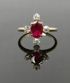 This antique ring has a nice, symmetrical, balanced shape and sits low on the finger, making it comfortable to wear. The center ruby has rich deep color and great clarity, accented nicely by four Antique Mine Cut diamonds.