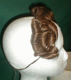 A unique 1830's false front hair piece that comes in its original box.  The hairpiece war worn by Mrs. Warren Birds.   Her name and information on how she wore it is written on the bottom of the box.  According to the note the piece was worn with a day cap and a large bonnet of the time period.   The light brown hair has an auburn tinge. It is attached to netting and has a tie back closure.  The hair piece is in very good condition.  There is some breakage on the box cover and some age…