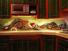 Kitchen backsplash mosaiced in broken china, glass tile and beads.
