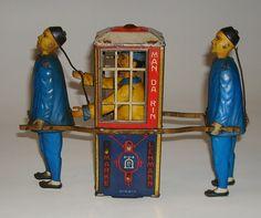 """1905 Lehmann """"Mandarin"""" tin toy.  Lengte 17,5 cm - hoogte 14cm - No.565 met uurwerkmotor ca. 1910. De jasjes van de dragers zijn handgeschilderd en de draagbalken van de koets zijn aan de buitenkant bevestigd. De """"mandarijn"""" in de draagkoets trekt de voorste koelie aan zijn vlecht."""