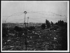 """Soldiers digging a trench.    """"In this photograph, which is similar to one by John Warwick Brooke, soldiers are shown digging a trench, viewed between strands of barbed wire. The men have only dug to about knee level and are very exposed, so it seems probable that they were not within sight of enemy trenches. Nearer the front line, trench digging was done under cover of night.    Barbed wire was used by both sides as a deterrent to slow an enemy attack as it approached the front of the…"""