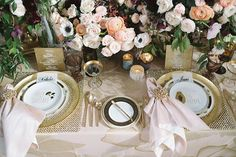 """Gold was the clear accent, with bullion details throughout the tabletop: from the chargers, rims of glassware, opulent napkin rings, calligraphy of the table numbers, glass menus, and more. See more of """"Hibiscus Glitz"""" on our blog (link in bio)! Designed by @agoodaffair + @littlehilldesigns using our Blush Hibiscus Linen with Blush Iridescence Dupionique Napkins. Rentals: @revelryleighc for@revelryeventdesign // China: @dishwishgirl // Bridal Gown: @jinzabridal // Lighting…"""