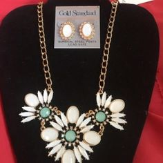 Statement necklace This statement necklace has beautiful white and aqua/gold colors it is a set and comes with surgical steel post lead free earrings. Brand-new original price $28. Gold Standard Jewelry Necklaces