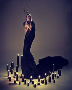 Black dress with train, antlers, and candles